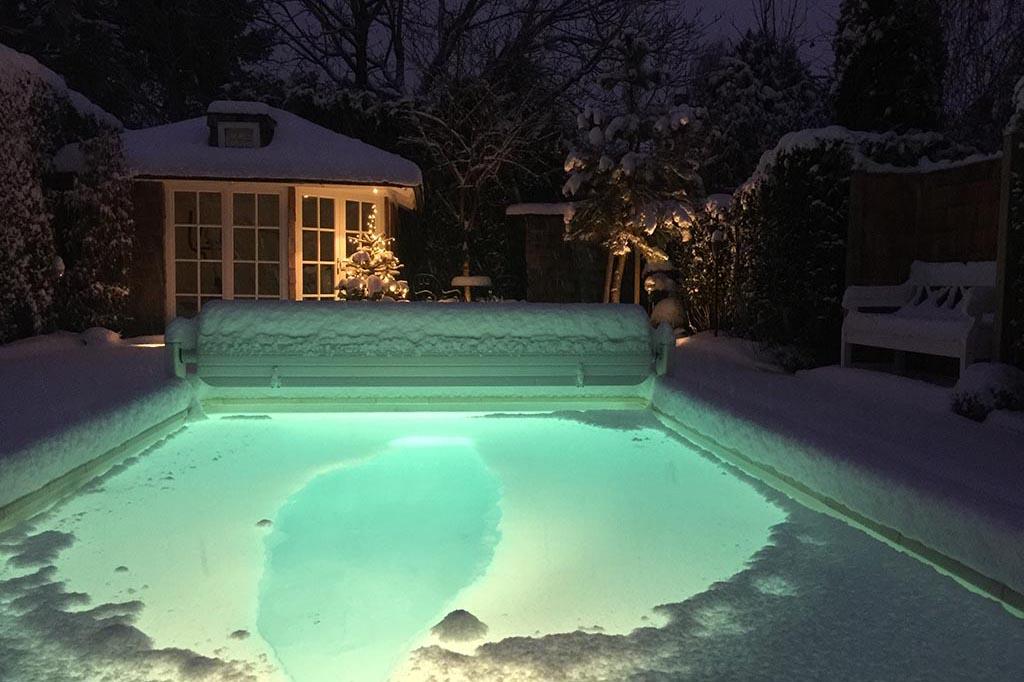 Swimmingpool mit Schnee nachts beleuchtet