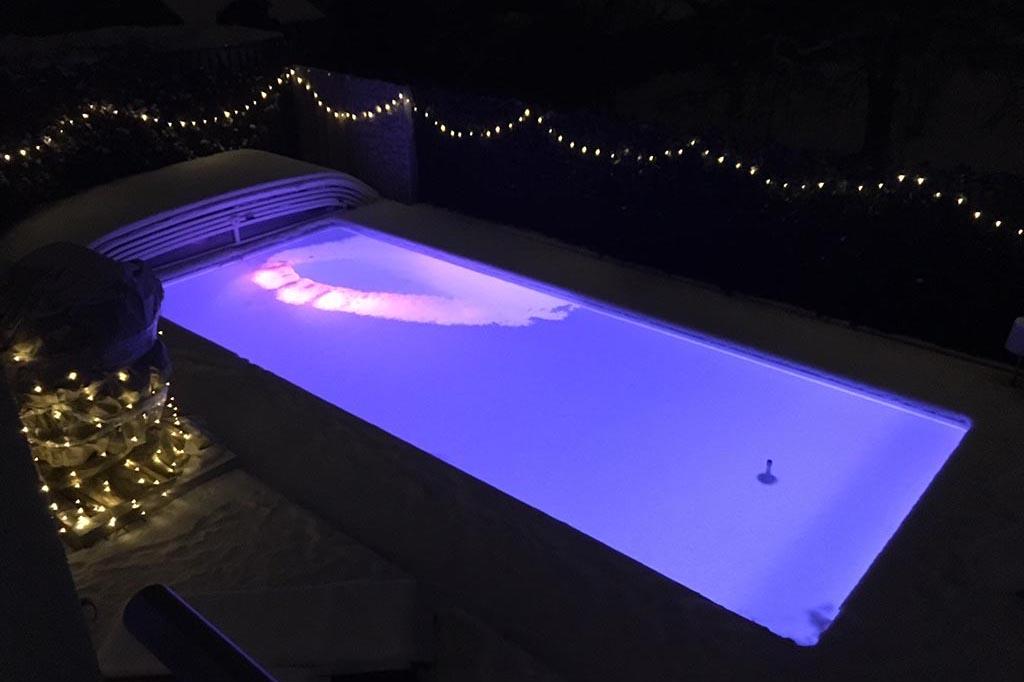 Pool mit Schneeschicht und Beleuchtung